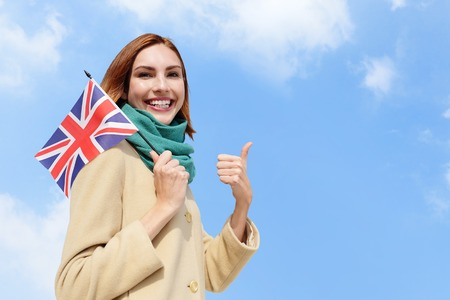 english girl: happy young travel woman holding British England flag with sky background, caucasian beauty