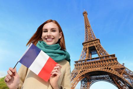 Gelukkige vrouw reizen in Parijs met de toren van Eiffel en mooie blauwe hemel en houden Frankrijk Franse vlag, Kaukasisch schoonheid Stockfoto