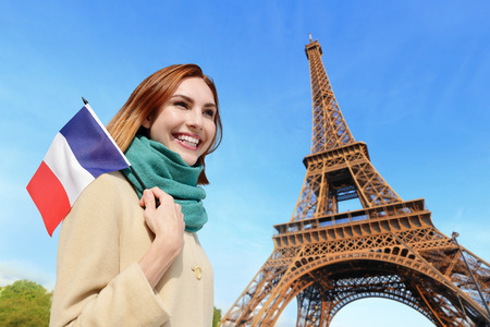 french woman: Happy woman travel in Paris with eiffel tower and beautiful blue sky and holding France French flag, caucasian beauty