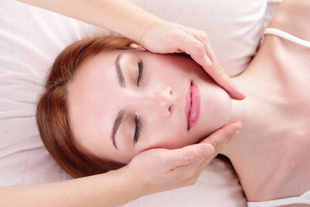 Beautiful young woman enjoy face massage at spa, caucasian beauty Stock Photo