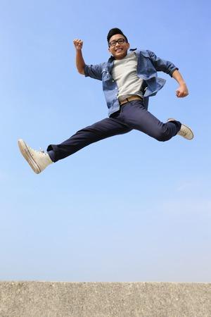 estudiante: Hombre feliz del estudiante universitario correr y saltar con fondo de cielo azul, de cuerpo entero, asi�tico macho