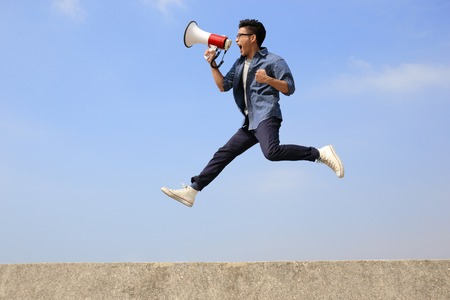 hombre saltar y gritar por megáfono con fondo de cielo azul, asiático