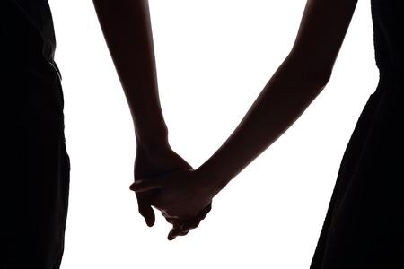 siluetas de enamorados: silueta de dos amantes se dan la mano juntos. Aislado en el fondo blanco Foto de archivo