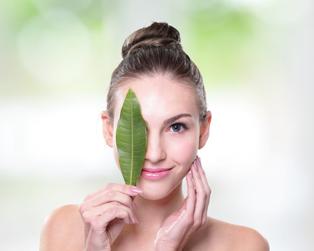 smiling faces: Skin care woman face with green leaf, concept for skin care or organic cosmetics, caucasian
