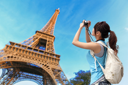 Happy travel woman in Paris with Eiffel Tower and she take a picture, asian beauty