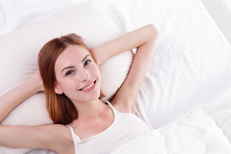european people: Close up of a happy young woman smile looking at camera while lying on the bed, isolated on white background , caucasian beauty