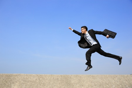air speed: business man jump and run on blue sky background