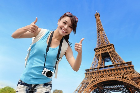 paris: Happy travel woman in Paris with Eiffel Tower and she show thumbs up