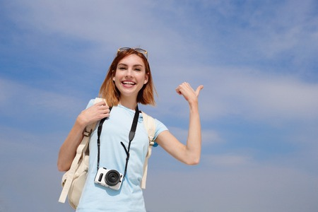 travel show: Happy travel woman smile to you and show something by finger with sky background, caucasian beauty