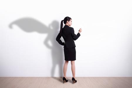 Back view of Superhero business woman writing something on white wall background Stockfoto