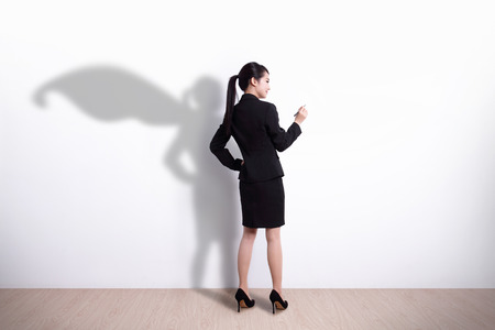 Back view of Superhero business woman writing something on white wall background Stock Photo