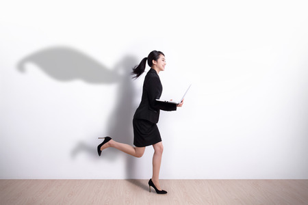 Great: Superhero business woman running and hold laptop computer with white wall background, great for your design or text, asian