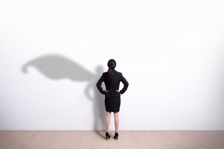 Back view of Superhero business woman look white wall background