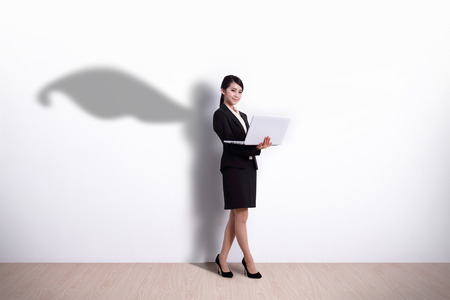 Superhero business woman using laptop computer with white wall background