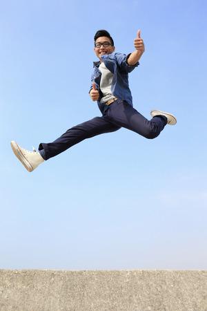 幸せな大学生の男は、青い空を背景にジャンプします。