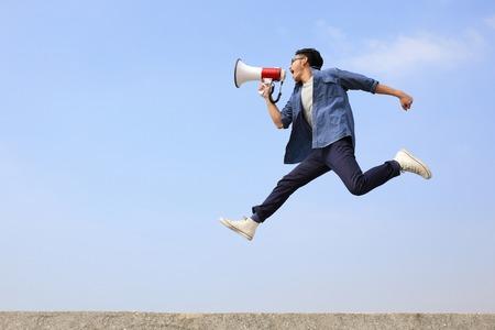 in jeans: hombre saltar y gritar por meg�fono sobre fondo de cielo azul