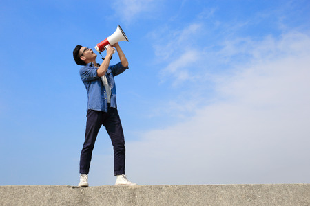 young man shout by megaphone with blue sky background, asian