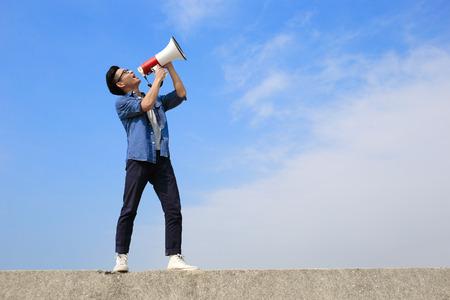 megafono: joven hombre grito por megáfono con fondo de cielo azul, asiático