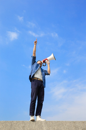 cheer full: young man shout by megaphone with blue sky background, asian