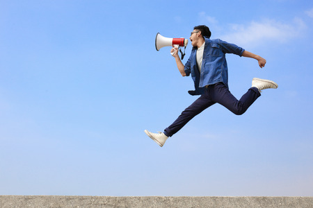 speaking: man jump and shout by megaphone with blue sky background, asian