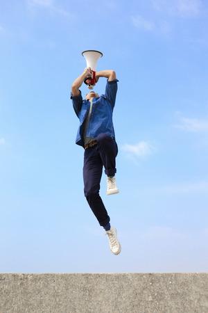 megafono: hombre saltar y gritar por megáfono con fondo de cielo azul, asiático