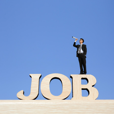 Human resource concept - business man stand on JOB text word with telescope ( spyglass ) and look for job photo