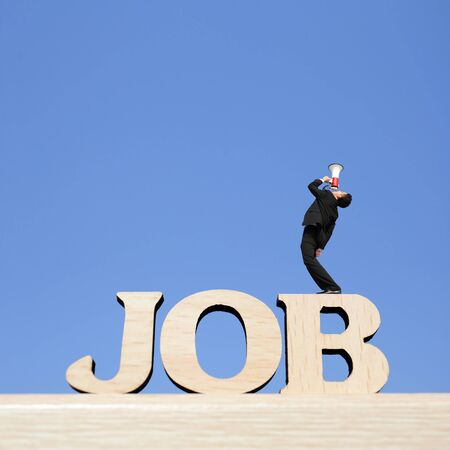 Human resource concept - business man stand on JOB text word and using megaphone shouting with blue sky background photo