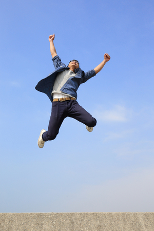 jump: Happy College student man run and jump with blue sky background, full length, asian male Stock Photo