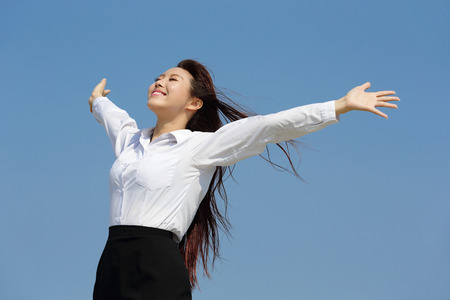 enjoy space: carefree business woman arms up and feel free isolated on blue sky background, asian beauty
