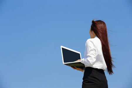 Successful business woman purposefully looking away and hold a computer with blue sky, asian beauty