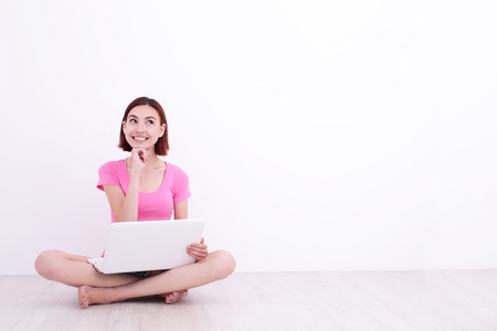 Happy smile young woman student girl using laptop computer pc and sit on the floor with white wall background, great for your design or text photo