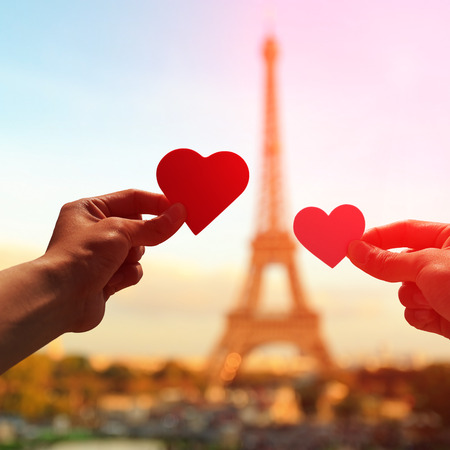 romance: silhueta de amantes românticos da preensão da mão de papel coração amor com a torre Eiffel em Paris, com o por do sol Banco de Imagens