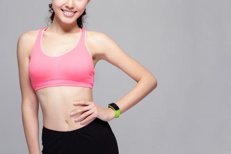 La mujer del deporte Salud vistiendo dispositivo reloj inteligente con pantalla táctil haciendo ejercicios aislados sobre fondo gris, belleza asiática