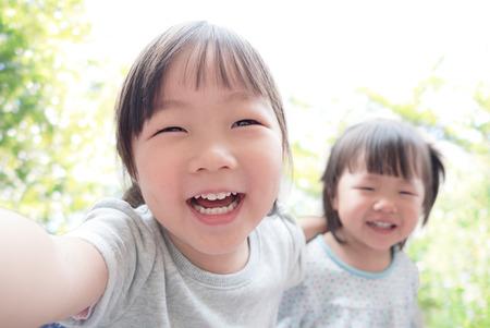 juventud: Niño feliz toma una Autofoto en el parque, asiático Foto de archivo