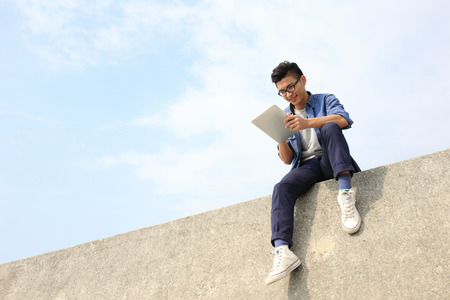 Happy College student man using digital tablet pc and sit, asian male Stock Photo
