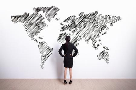 mundo manos: Volver la vista de mujer de negocios de mirada dibujo a mano mapa del mundo, asiático