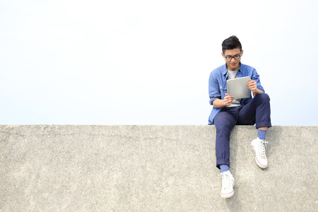 Gelukkig College student man met behulp van digitale tablet pc zitten, Aziatische mannen Stockfoto