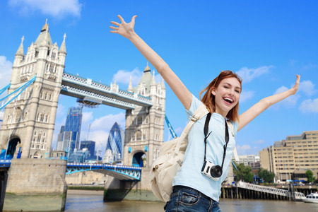 travellers: Happy woman travel in London with tower bridge, and smile to you, caucasian beauty Stock Photo
