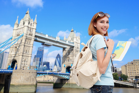 Happy woman travel in London with tower bridge, and smile to you, caucasian beauty 스톡 콘텐츠