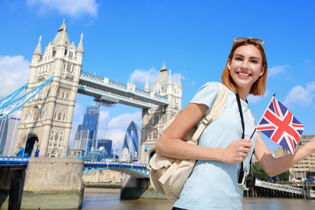 travel guide: Happy woman travel in London with tower bridge, and smile to you, caucasian beauty Stock Photo