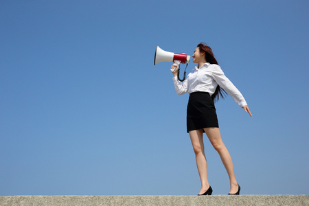 happy asian people: Successful business woman shouting in megaphone with blue sky background