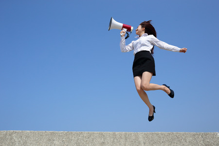 Successful business woman shouting in megaphone with blue sky background