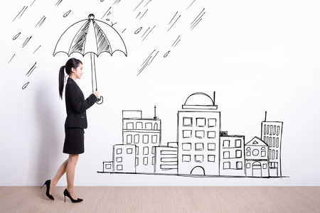 protect: business woman walking and holding drawing umbrella with white wall background Stock Photo