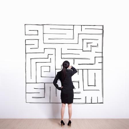 the maze: Volver la vista de mujer de negocios aspecto gr�fico de la mano laberinto con pared blanca de fondo, asi�tico Foto de archivo
