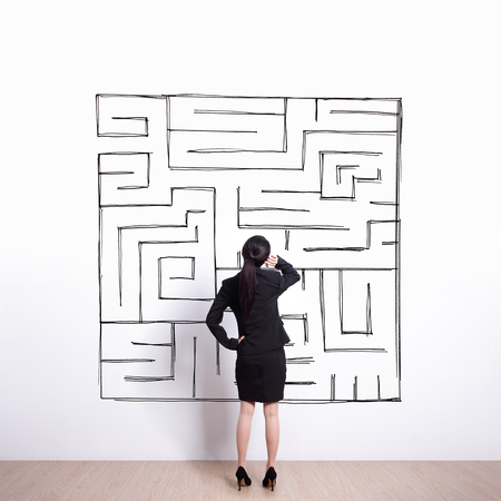 Vue arrière de la femme d'affaires regard main dessin labyrinthe avec mur blanc fond, asiatique