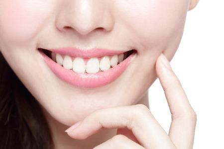 dentisterie: Belles jeunes dents de la santé de la femme se referment et charmant sourire. Isolé sur fond blanc, la beauté asiatique