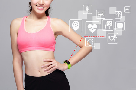 blood sport: Health sport woman wearing smart watch device with health icon isolated on gray background, asian beauty Stock Photo