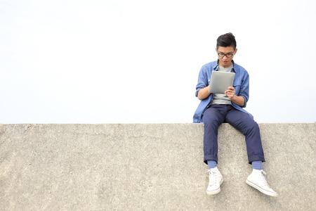 デジタル タブレット pc と座って、アジア人の男性を使用して幸せな大学生男