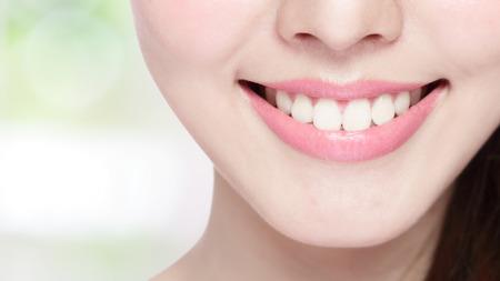 dentaire: Belles jeunes dents de la santé de la femme se referment et charmant sourire. Isolé sur fond vert, la beauté asiatique