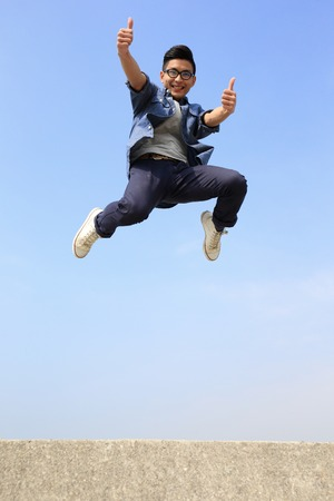 air jump: Happy College student man run and jump with blue sky background, full length, asian male Stock Photo